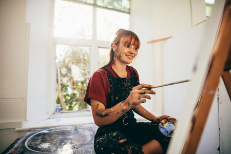 Female artist painting in studio