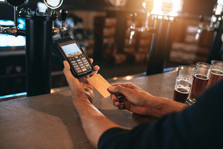 Man paying using a credit card at bar