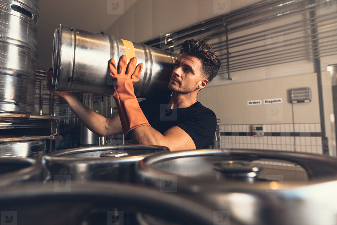 Brewer carrying metal beer barrel at brewery factory