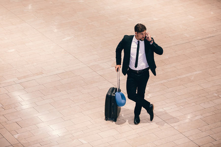 Business traveler making a phone call while waiting for flight
