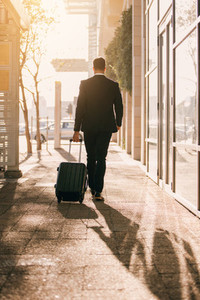 Business traveler with suitcase outside airport