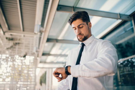 Business executive checking time outside airport