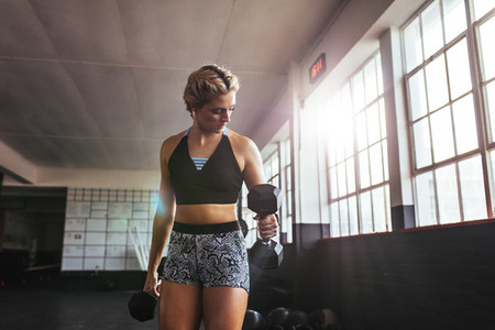 Female athlete working out at the gym using dumbbells