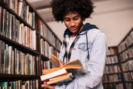 University student standing in library with lots of books
