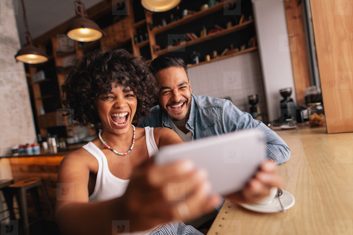 Happy couple sitting together at cafe and taking selfie