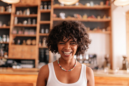 Happy young woman laughing in a cafe