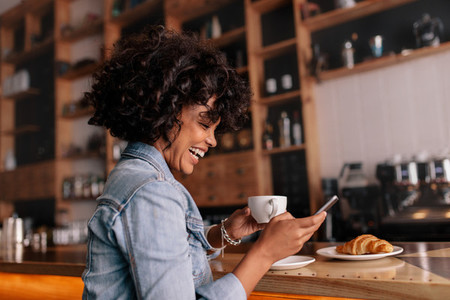 African woman cafe using mobile phone and smiling