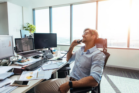 Business investor in a happy mood talking over phone in office