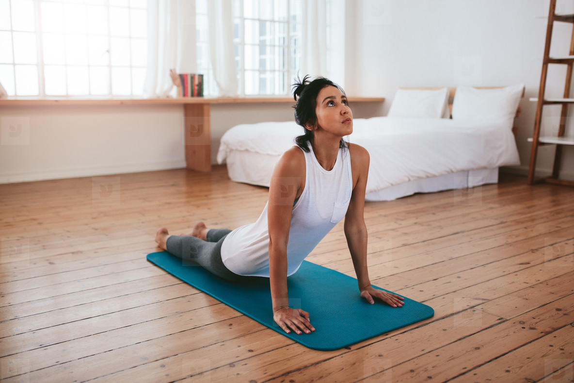 Fitness woman practising yoga at home
