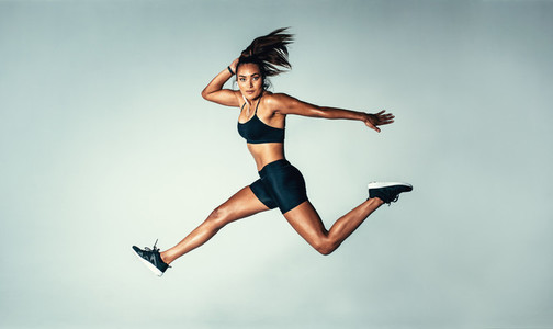 Female model in sports wear jumping in air