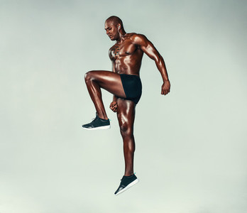 Fitness man jumping and stretching over grey background