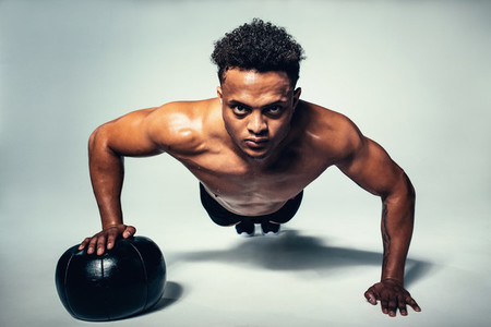 Muscular young man doing push up on medicine ball