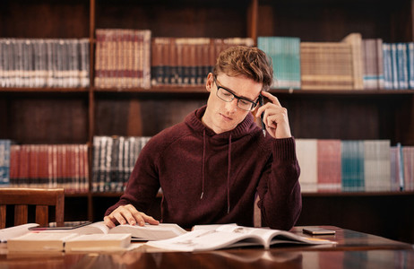 Young student preparing for exam in library
