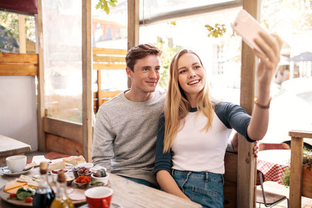 Couple taking photos of themselves in cafe