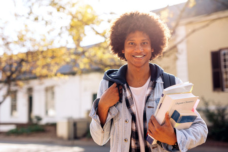 College student with lots of books in college campus