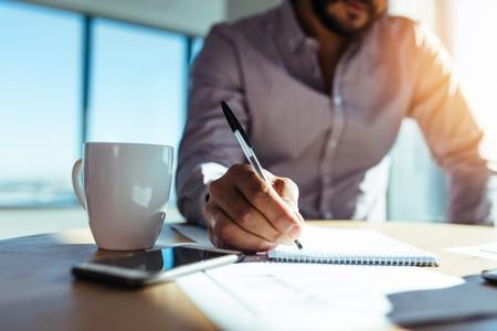 Businessman making notes at his desk