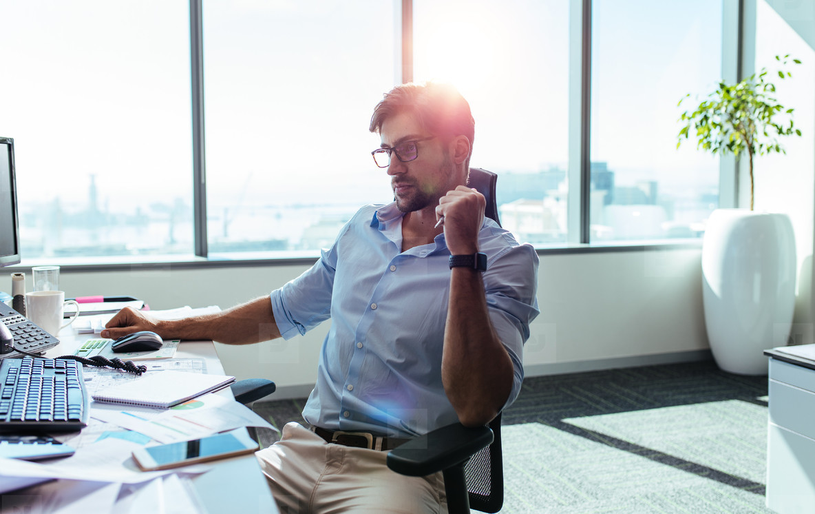Businessman sitting at his work station in office