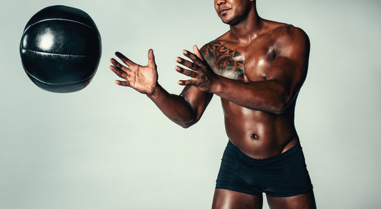 Healthy young man exercising with medicine ball