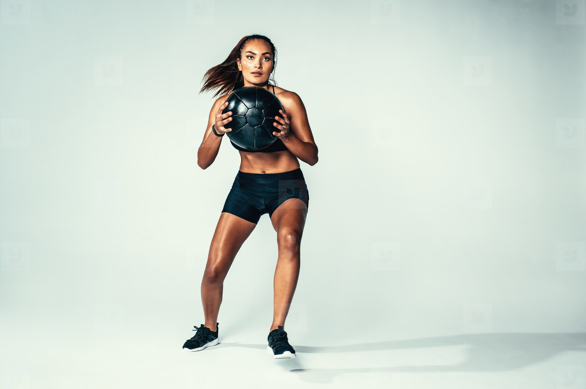 Fit young woman exercising with medicine ball