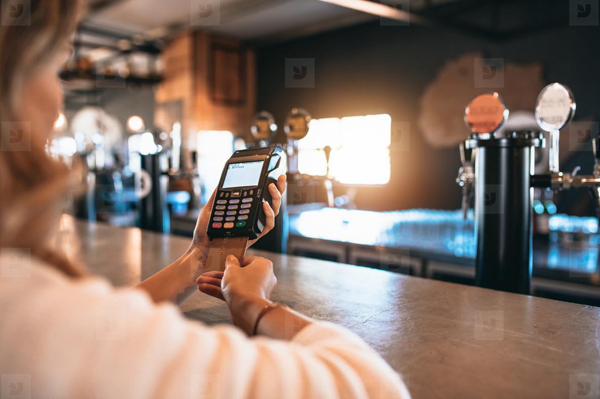 Woman paying bill using a credit card at bar