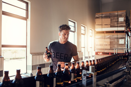 Businessman testing the beer bottle at brewery
