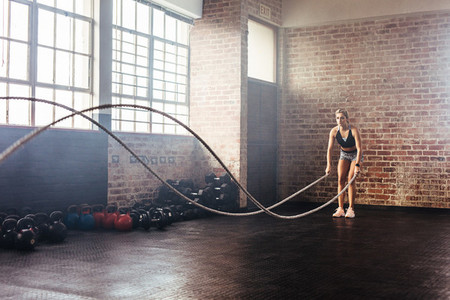 Athlete exercising in gymnasium using training ropes