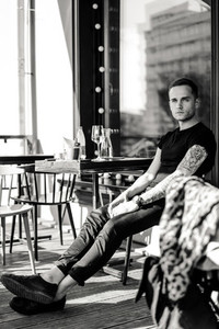 Handsome tattooed man on a summer terrace in a city cafe is drin