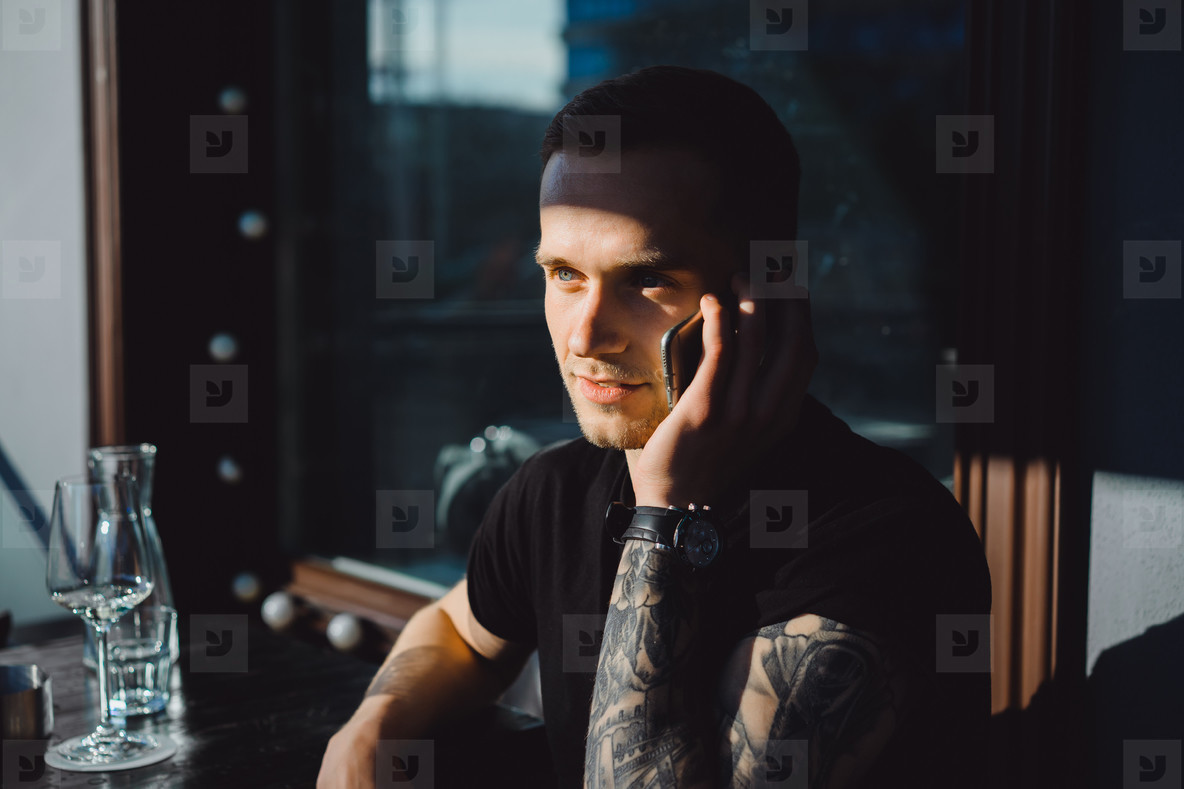 Handsome tattooed young man talking on the phone  close up portr
