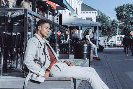 Stylish young African American man posing in a street cafe