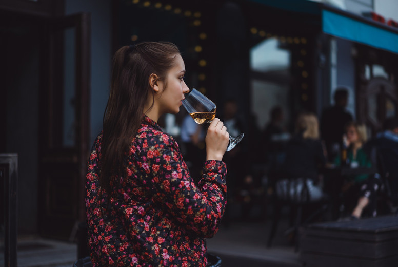 Stylish young girl drinks wine in a street cafe on a summer terr