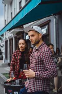 A man and a girl are drinking wine on a summer terrace in a stre