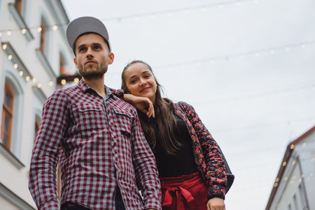 Stylish young couple posing outdoors A young man with a bristle