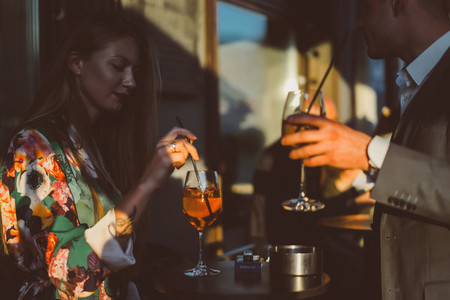 Man and woman drink cocktails in a street cafe on the summer ter