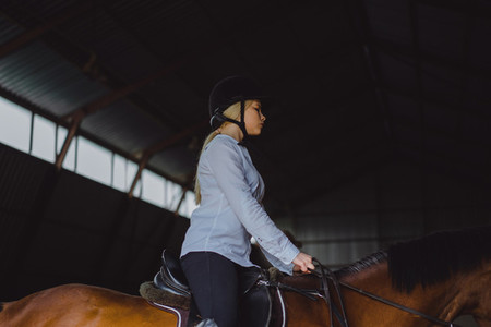 A girl on horseback riding an arena