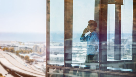Businessman inside office building talking on mobile phone
