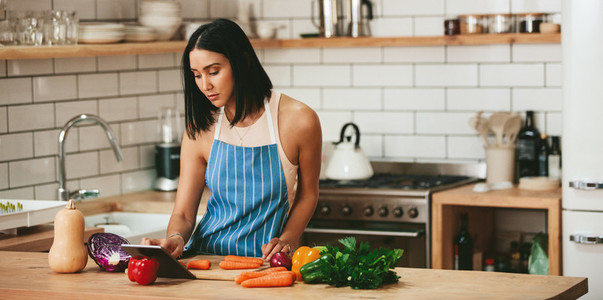 Beautiful woman watching recipe to prepare food in kitchen