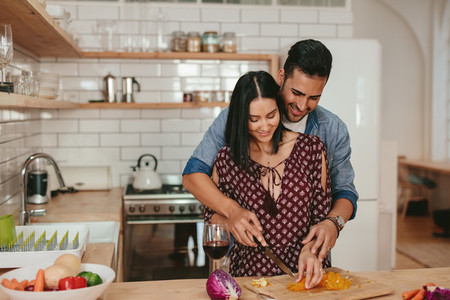 Romantic couple cooking in kitchen at home