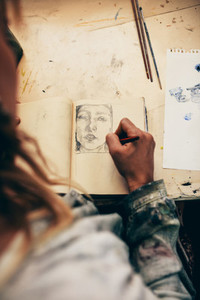 Woman artist sketching on book