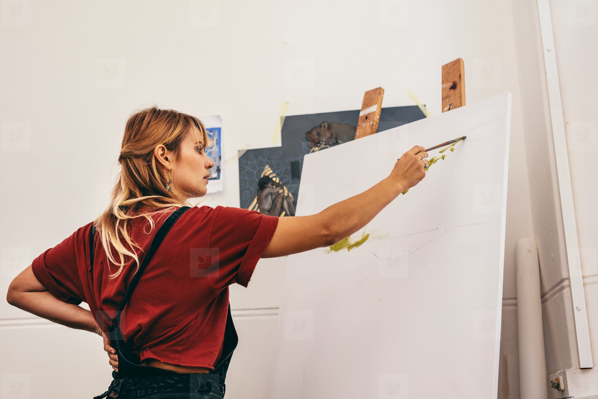 Woman artist painting a picture in studio