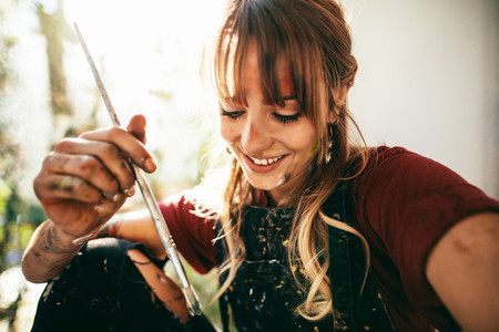 Beautiful young woman artist with paint brush