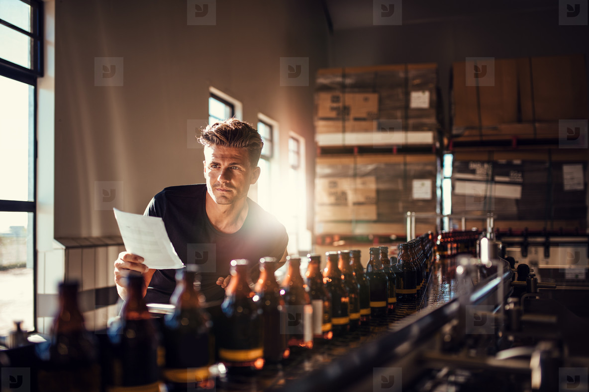 Worker checking the process on the production line in brewery fa