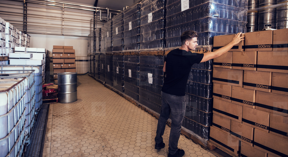 Brewery owner verifying the beer boxes in delivery storage area