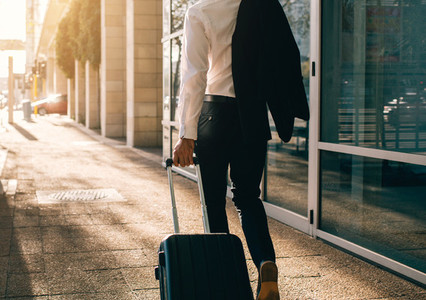 Businessman walking outside airport with suitcase