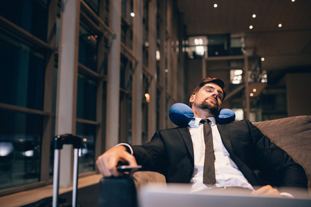 Young businessman asleep in airport lounge