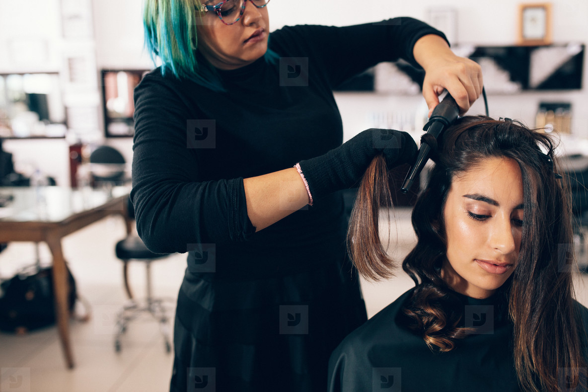Hair stylist makes a curls for woman in salon