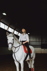 A girl on horseback riding an arena