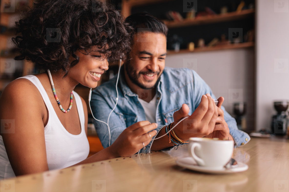 Happy couple at cafe having video chat on mobile phone