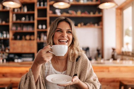 Smiling young woman having coffee