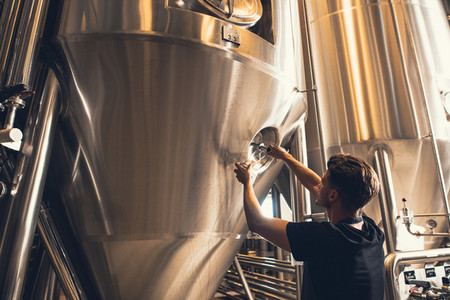 Brewer working with industrial equipment at the brewery