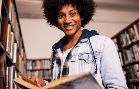 Young black man with book in college library